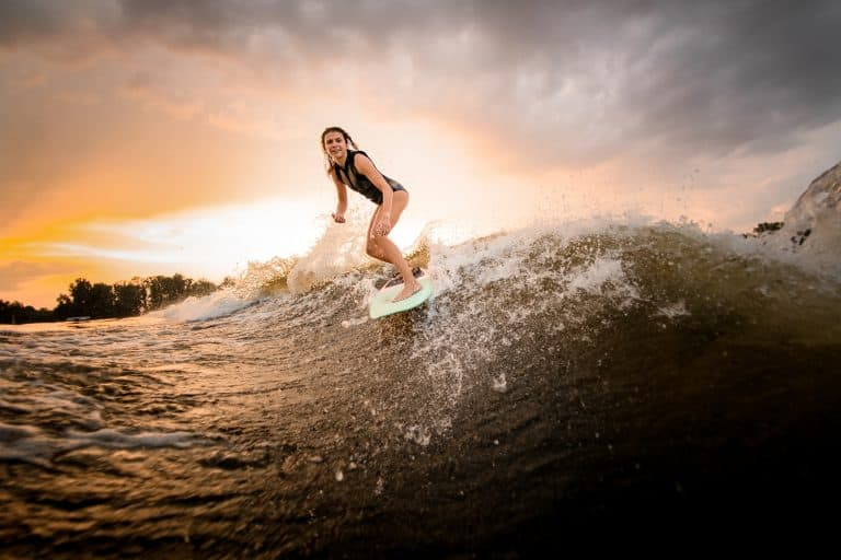 Girl riding on the wakesurf board on the river on the wave in the background of the sunset and trees