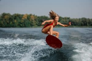Attractive blonde girl jumping on the red wakeboard